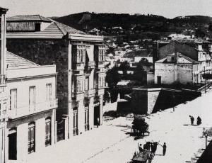 La calle García Barbón con las casas que existían antes de la construcción de las Casas de Oya ( hoy hotel NH ) y a su derecha vista del espacio por donde salía el tren. Fotografía tomada del libro Vigo
