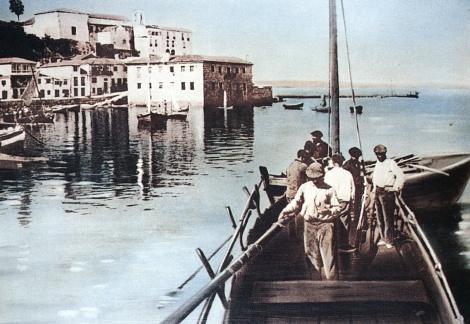 Marineros llegando a puerto. Al otro lado de la playa se ven el antiguo matadero municipal pegado al borde del mar y a su izquierda el convento de San Francisco. Fotografía coloreada de Pacheco